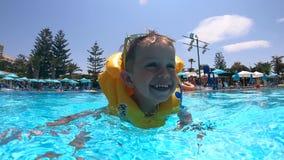 Ett barn i en flytväst simmar lyckligt i pölen stock video