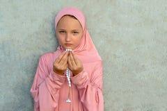 Ett barn i en rosa hijab med p?rlor i hans h?nder med kopieringsutrymme Religi?st livsstilbegrepp f?r folk arkivbild