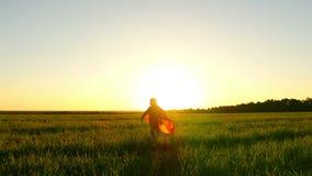 Ett barn i en superherodräkt kör på en grön gräsmatta mot bakgrunden av en solnedgång som hittar på flyg, på en långsam hastighet stock video
