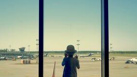 Ett barn i flygplatsen En pojke ser flygplatslandningsbanan till och med fönstret arkivfilmer