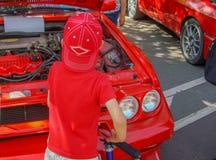 Ett barn i röd kläder undersöker motorn av bilen royaltyfria foton