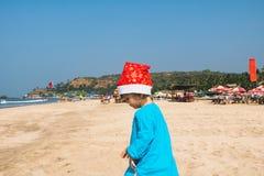 Ett barn i Santa Claus kläder, jul på ett tropiskt hav är Arkivfoton