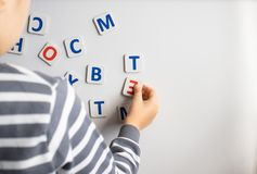 Ett barn lär bokstäverna på svart tavla Pojken studerar bokstäverna royaltyfria bilder