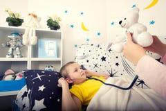 Ett barn lyssnar till en leksakbjörn med en phonendoscope fotografering för bildbyråer
