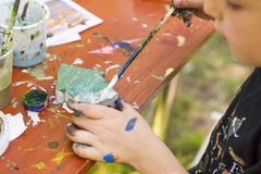 Ett barn med en borste i hans hand målar en leksak Barn med tofsen i bilden fotografering för bildbyråer