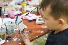 Ett barn med en borste i hans hand målar en leksak Barn med tofsen i bilden arkivbild
