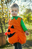Ett barn med en pumpamaskeradkläder. Halloween arkivfoton