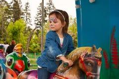 Ett barn på en karusell i parkera Royaltyfria Bilder