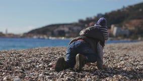Ett barn på stranden kryper på kiselstenar arkivfilmer