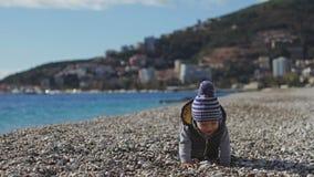Ett barn på stranden kryper på kiselstenar lager videofilmer