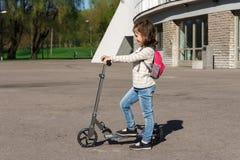 Ett barn rider en sparkcykel Royaltyfri Foto