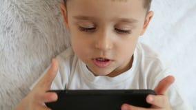 Ett barn rymmer en smartphone främst av honom, och att spela spelar i ultrarapid på en vit bakgrund arkivfilmer