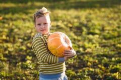 Ett barn rymmer en stor orange pumpa royaltyfri bild