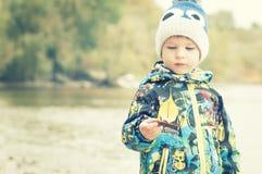 Ett barn rymmer ett fartyg från ett höstblad, ett begrepp, en instagram Arkivfoto