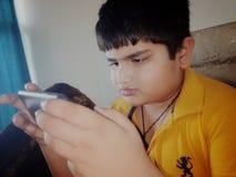 Ett barn som fängslas i en mobil grej royaltyfria foton