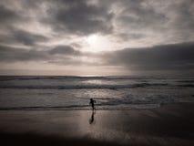 Ett barn som kör på stranden med hisnande mörka moln royaltyfri fotografi