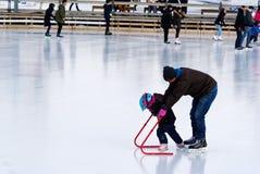 Ett barn som lär att åka skridskor på en utomhus- isbana i Montreal royaltyfri bild