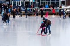 Ett barn som lär att åka skridskor på en utomhus- isbana i Montreal royaltyfria bilder