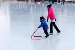 Ett barn som lär att åka skridskor på en utomhus- isbana i Montreal royaltyfri foto