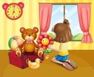 Ett barn som ordnar hennes leksaker inom huset Arkivbild