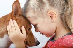 Ett barn som rymmer ett huvud för hund` s arkivfoton