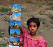 Ett barn som säljer vykort på Bagan tempel i Bagan, Myanmar Royaltyfria Bilder