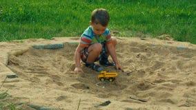Ett barn som spelar i sandlådan lager videofilmer