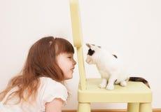 Ett barn som spelar med en vit kattunge Royaltyfria Bilder