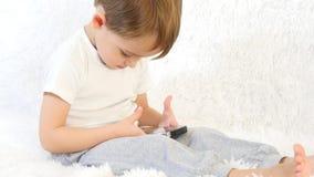Ett barn som spelar med ett smartphonesammanträde på en vit bakgrund Närbild lager videofilmer
