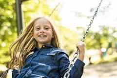 Ett barn som spelar på lekplatshöstsäsongen arkivfoton
