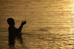 Ett barn som tycker om havet under solnedgång Royaltyfri Fotografi