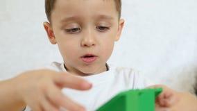 Ett barn spelar i färgkvarter som sitter på en tabell på en vit bakgrund, i ultrarapid Barn och leksaker Närbild lager videofilmer