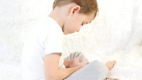 Ett barn spelar med en smartphone som sitter på en vit bakgrund Närbild stock video