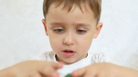Ett barn spelar med kulöra kvarter och att bygga ett hus som sitter på en tabell på en vit bakgrund, närbilden lager videofilmer