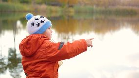 Ett barn står på banken av dammet och kastastenar Går i den nya luften Arkivfoto