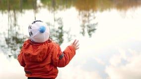 Ett barn står på banken av dammet och kastastenar Går i den nya luften arkivfilmer