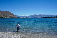 Ett barn undersöker det härliga vattnet av sjön Wanaka, Nya Zeeland royaltyfri fotografi