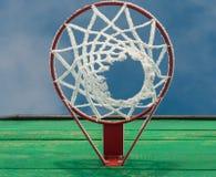 Ett basketbeslag med ett netto i frosten på bakgrundsslut för blå himmel sköt upp underifrån Arkivfoton