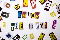 Ett begrepp för visning för ordhandstiltext av Enjoy som dagen gjorde av den olika tidskrifttidningsbokstaven för affärsfall på d arkivbilder
