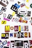 Ett begrepp för visning för ordhandstiltext av mobila bankrörelsen som göras av den olika tidskrifttidningsbokstaven för affärsfa Arkivfoto