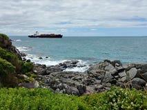 Ett behållareskepp lämnar hamnen av bluffen, Nya Zeeland royaltyfri foto