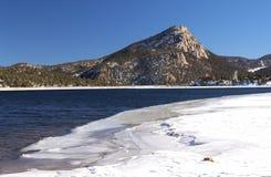 Ett bergmaximum som beskådas från över den delvist fryste sjön Estes Royaltyfri Bild