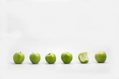 Ett bitit äpple i en linje av hela gröna äpplen Arkivfoto
