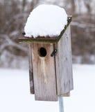 Ett blåsångarehus med snö på taket Arkivfoton