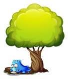 Ett blått monster som skrivar ett brev under trädet Arkivfoton