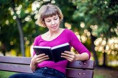Ett blond kvinnasammanträde och läsning en bok i parkera Folk l royaltyfri bild
