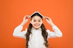 Ett boktak över hennes huvud Liten flicka som rymmer textboken på huvudet Liten flicka med barns bok på orange bakgrund royaltyfri bild