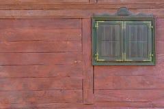 Ett brunt fönster på en röd träkabinvägg royaltyfria foton