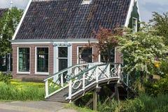 Ett brunt hus nära den lilla vita bron med gröna träd runt om den Arkivfoton