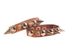 Ett brunt läderarmband med grova spikar Royaltyfri Bild